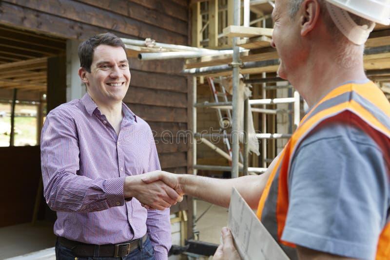 顾客与建造者握手 免版税库存图片