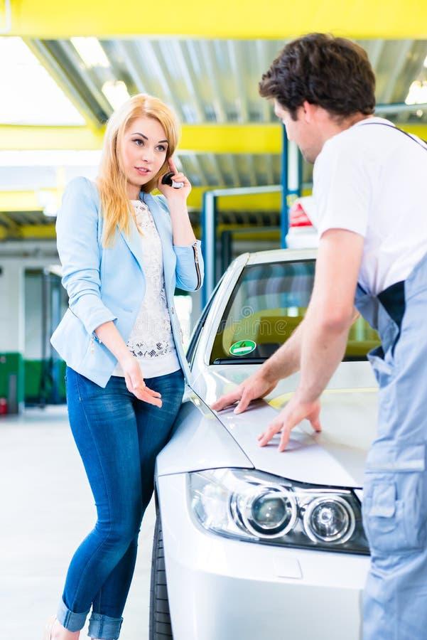 顾客和汽车画家在自动车间 免版税库存图片