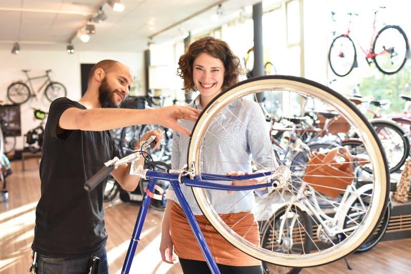 顾客和经销商在自行车商店-购买和自行车修理-顾客服务 库存照片