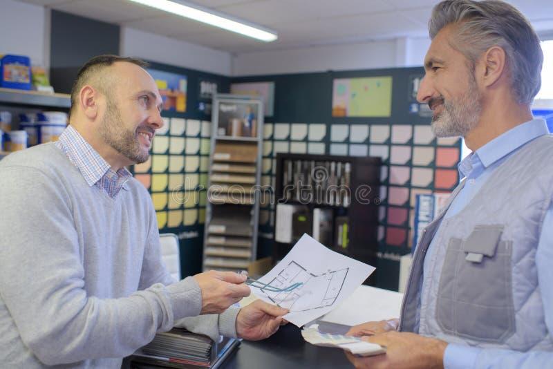 顾客和设计师谈论项目在机构中 免版税图库摄影