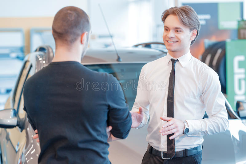 顾客和销售顾问有陈列室视图 免版税库存图片