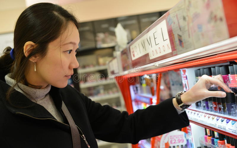 顾客在化妆用品商店浏览一个架子 免版税库存图片