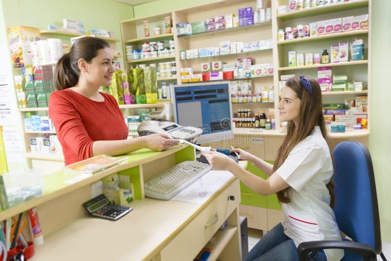 顾客在拿着收据的药房 库存图片