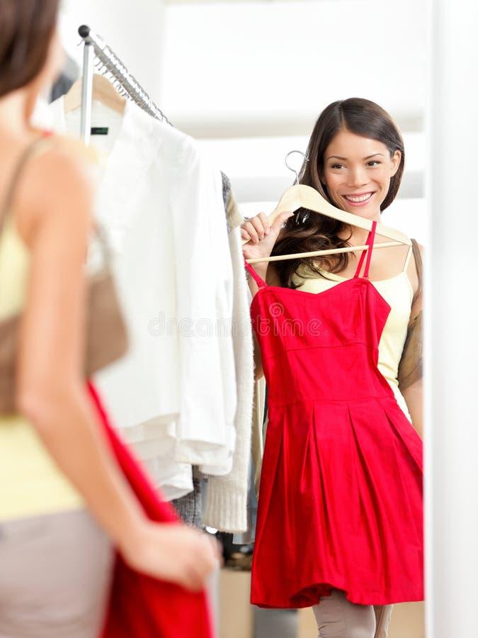 顾客妇女尝试的衣物礼服购物 库存图片