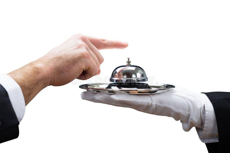 顾客敲响的服务侍者举行的响铃 免版税库存图片