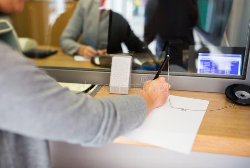 顾客文字应用在银行办公室 免版税库存照片