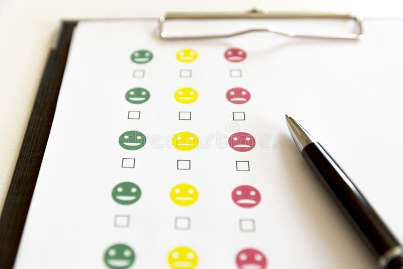 顾客服务与兴高采烈的面孔和笔的评估调查 库存图片