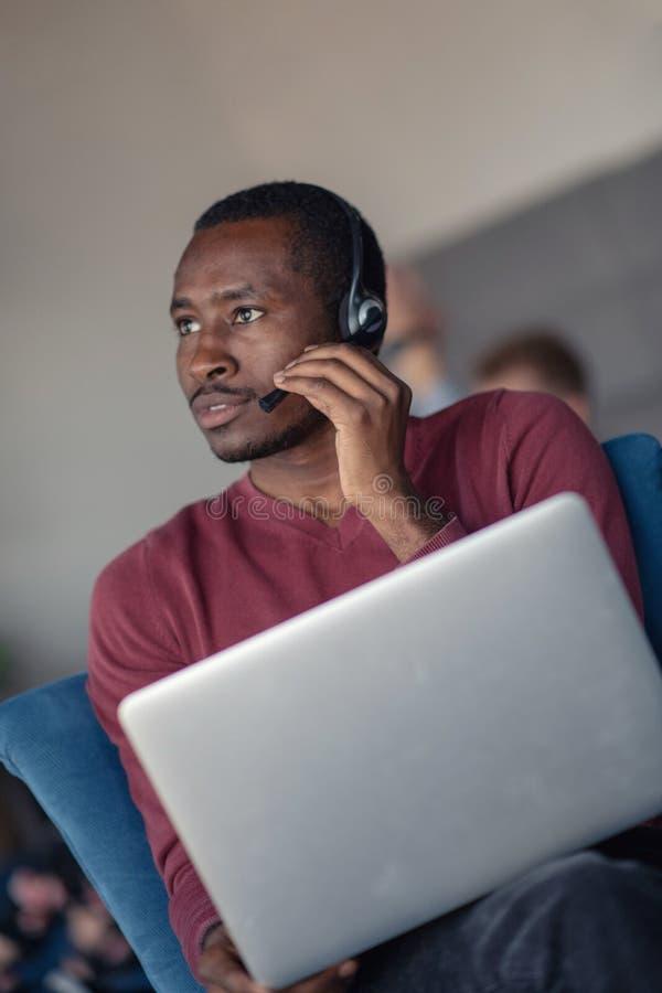 顾客服务代理在有膝上型计算机的一个起始的办公室 免版税库存图片