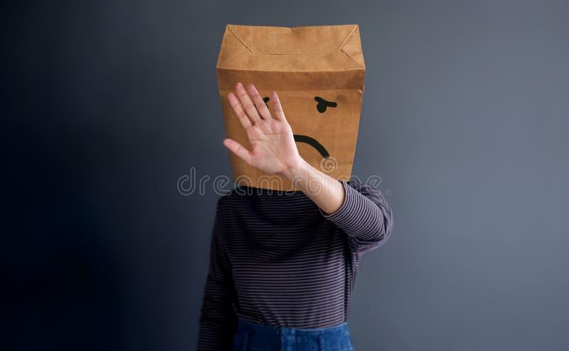 顾客经验或人的情感概念 妇女由提出她哀伤的感觉的纸袋的被盖的面孔 图库摄影