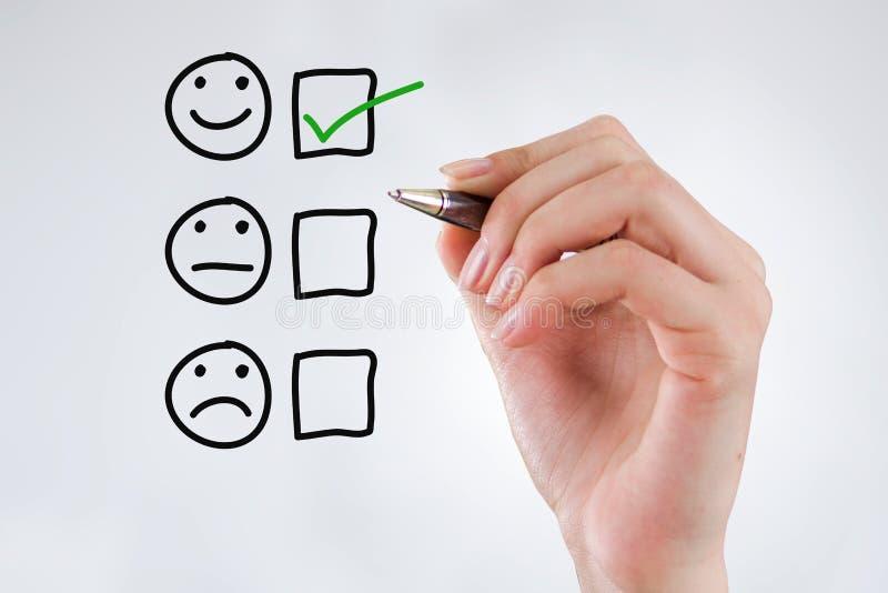 顾客经验概念,有一支笔的手与在优秀兴高采烈的面孔规定值的一个复选框满意调查的 免版税图库摄影