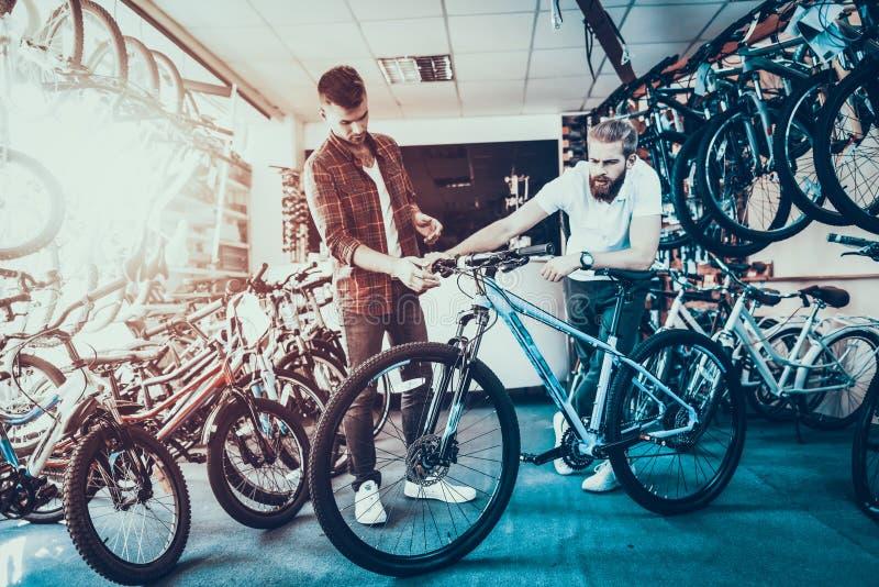 顾问显示自行车给客户在体育商店 免版税图库摄影