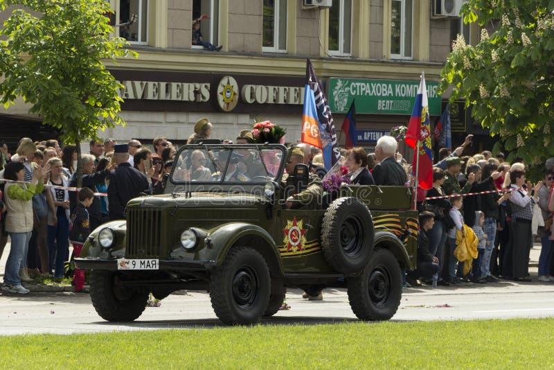 顿涅茨克人共和国,乌克兰 2016年, 5月9日 - 二战骑马的俄国军事退伍军人在老汽车的在胜利游行 库存照片