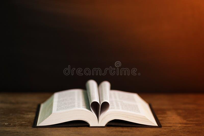预定在心脏形状的页有黑暗的背景 库存照片