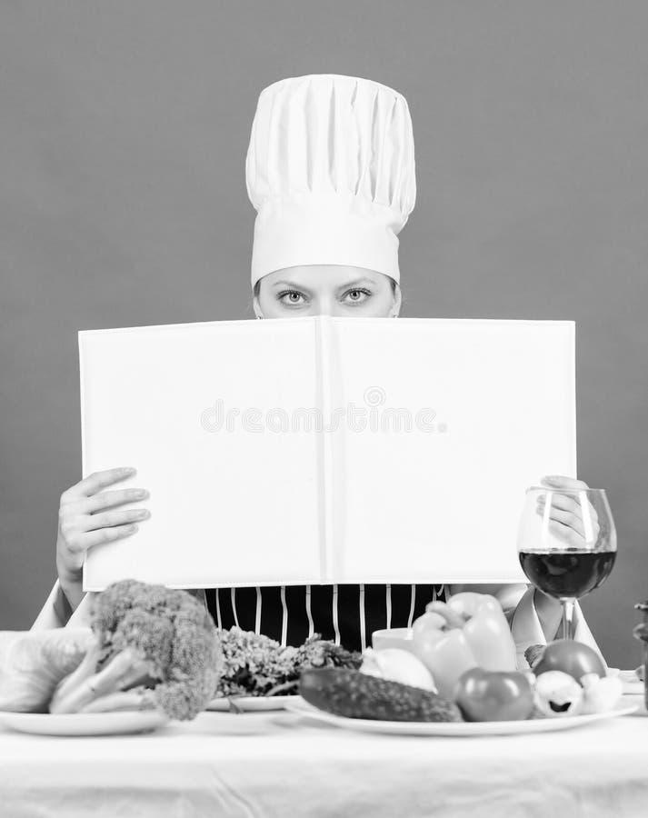 在图书馆里预订每一位家庭主妇 美女在厨房看书 厨女学新菜 库存图片