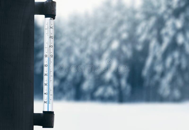 预测和冬天风化季节,在玻璃窗的温度计有被弄脏的多雪的冬天森林背景 免版税图库摄影