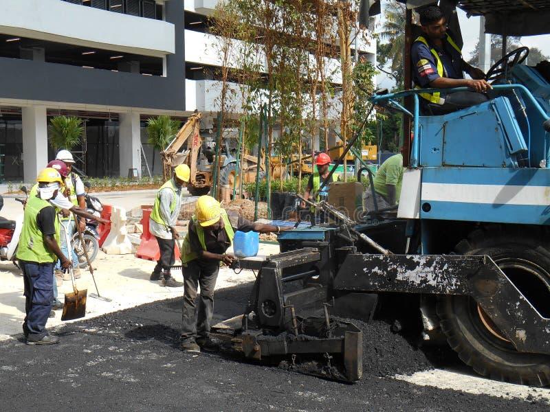 预混合料工作在建筑工人旁边 免版税库存图片