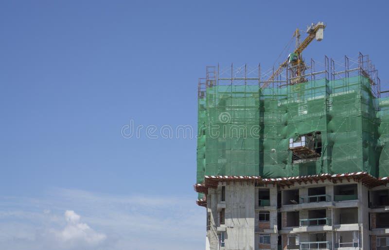 预铸的修造的盖子向上看法由绿色网,在建筑工作的大高塔吊移动的机器的,在清楚的蓝色下 免版税库存图片