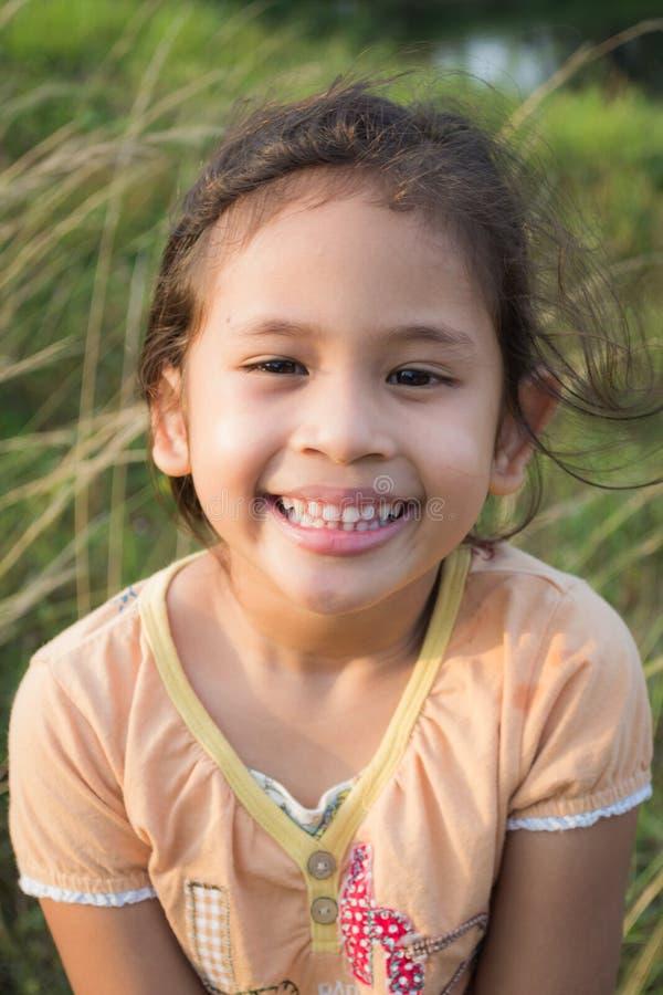 领域的一个微笑的逗人喜爱的女孩 免版税图库摄影