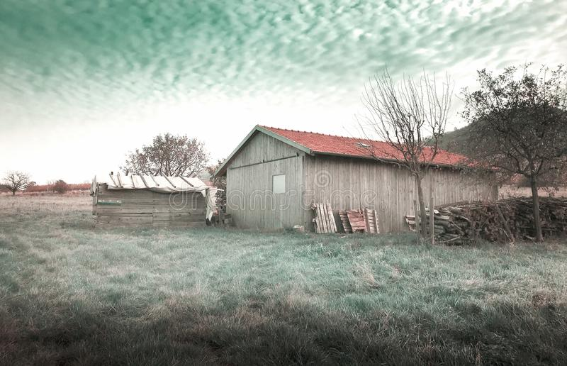 领域的偏僻的谷仓在抽象绿色天空前面 免版税图库摄影