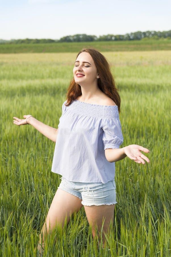领域的愉快的美丽的女孩享受自然的 免版税库存照片