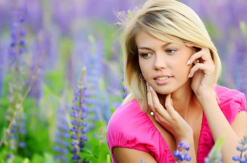 领域的美丽的妇女与羽扇豆 库存照片