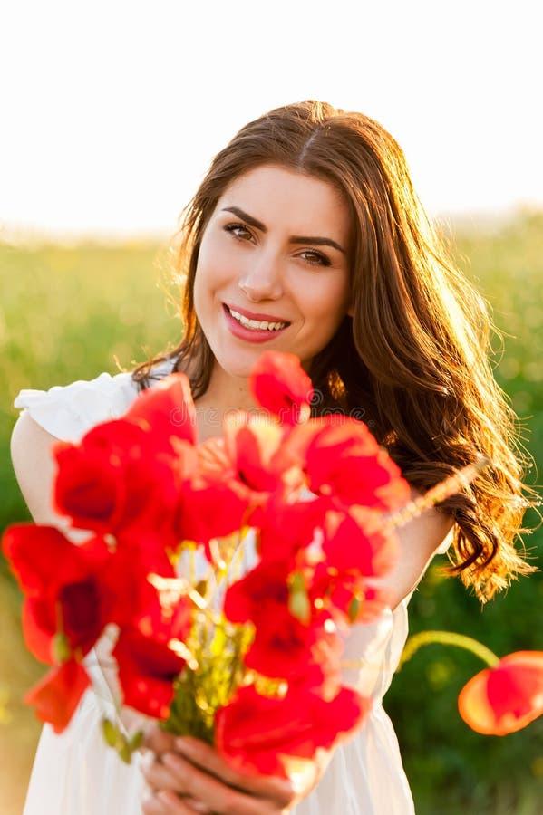 领域的年轻美丽的女孩与鸦片花束 库存照片