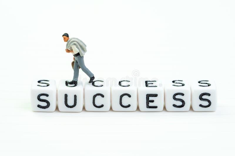 领导、企业或者事业成功概念,微型图走确信的商人在与字母表的白色立方体块 免版税库存照片