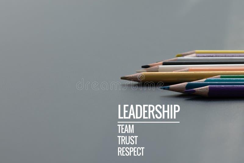 领导企业概念 金子颜色铅笔芯与词领导、队、信任和尊敬的其他颜色在黑背景 免版税库存照片