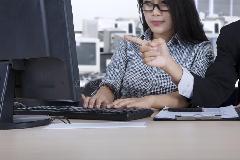 领导和助理有计算机的在工作场所 库存图片