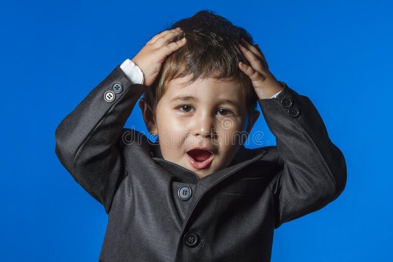 领导,在蓝色色度背景的逗人喜爱的小男孩画象 免版税库存照片