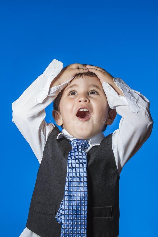 领导,在蓝色色度背景的逗人喜爱的小男孩画象 免版税库存图片
