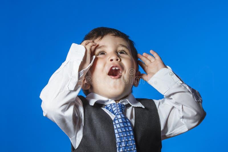 领导,在蓝色色度背景的逗人喜爱的小男孩画象 库存图片