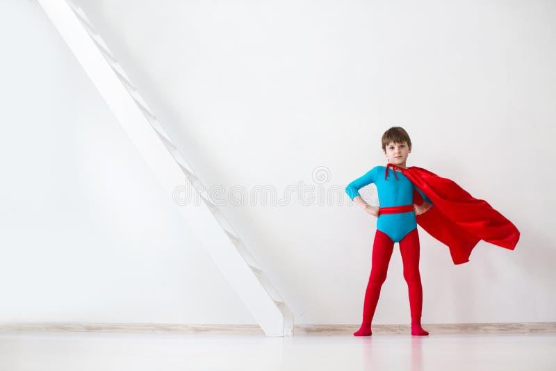 领导 一个红色斗篷的男孩特级英雄 免版税库存照片