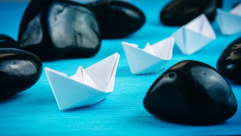领导主角进一步白皮书运送在蓝色背景的石头之间 从右到左移动 免版税图库摄影
