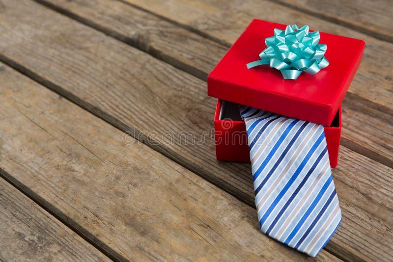 领带大角度看法在红色礼物盒的在桌上 免版税库存图片