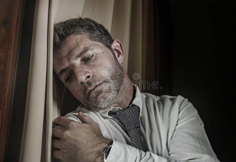 领带感觉被挫败的遭受的消沉和问题倾斜的年轻哀伤和沮丧的商人被淹没在窗口 库存图片