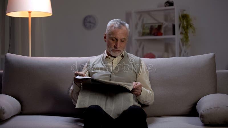领抚恤金者读书报纸在晚上,学会前超大事件,爱好 免版税库存照片