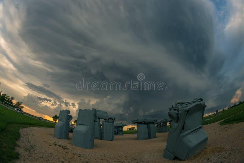 题为'Carhenge的'内布拉斯加旅游景点与严重雷暴在背景中 库存图片