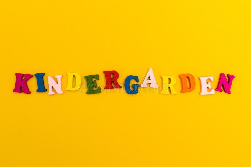 题字'幼儿园'在黄色背景的五颜六色的信件的 库存图片