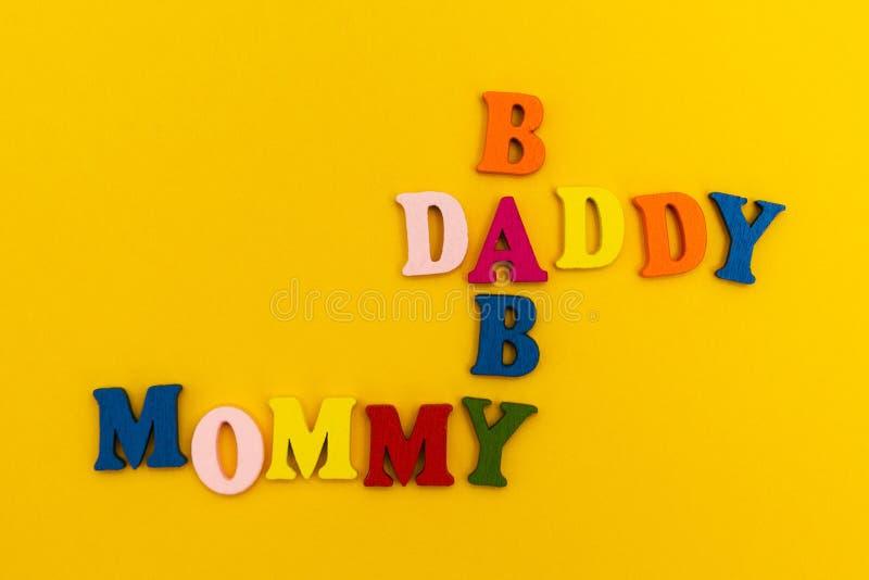 题字'爸爸,妈妈,婴孩'在黄色背景的五颜六色的信件的 图库摄影