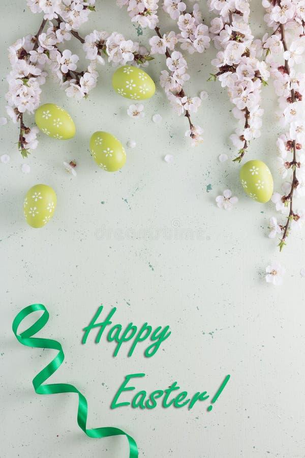 题字与鲜绿色的丝带的复活节快乐与花和复活节彩蛋 免版税库存图片