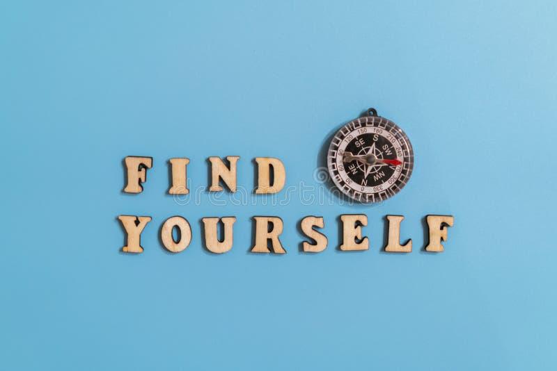 题字发现自己在蓝色背景的和指南针 显示在生活中和发现您的命运的概念 免版税图库摄影