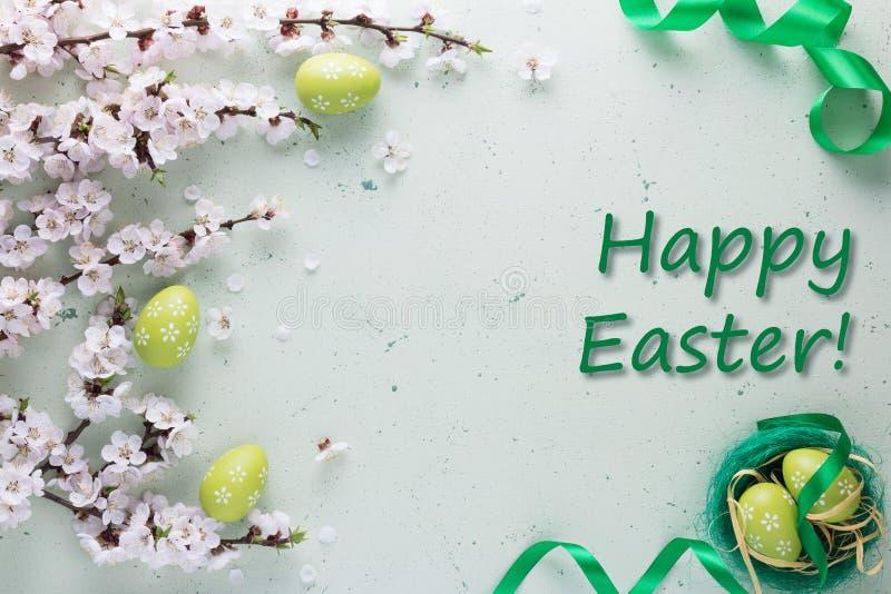 题字在用与花和复活节彩蛋的鲜绿色的丝带装饰的轻的背景的复活节快乐 图库摄影