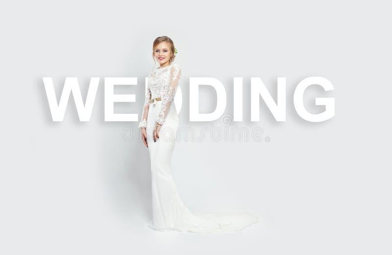 题字婚礼在妇女后一件白色礼服白色背景位于演播室 新娘女孩微笑 免版税库存图片