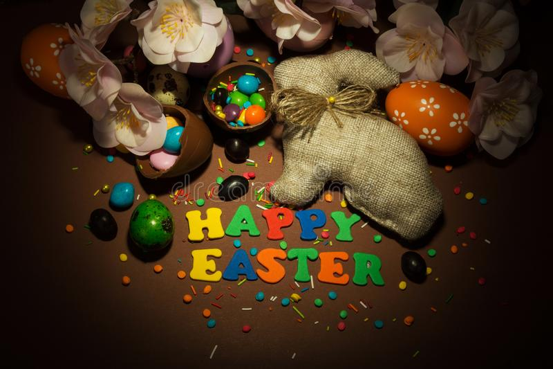 题字愉快的复活节、兔宝宝,复活节彩蛋、糖衣杏仁和得体 免版税库存照片