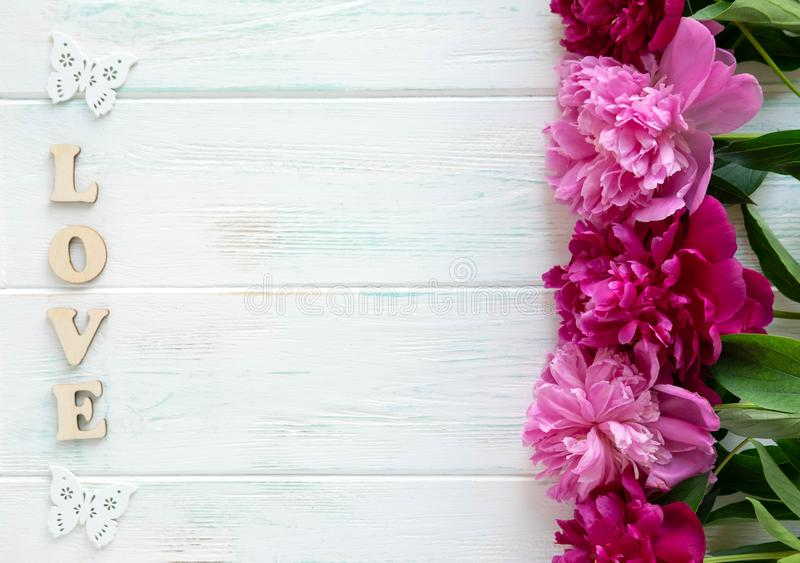 题字爱 牡丹花束在木背景的与题字 在轻的背景的桃红色和褐红的牡丹 图库摄影