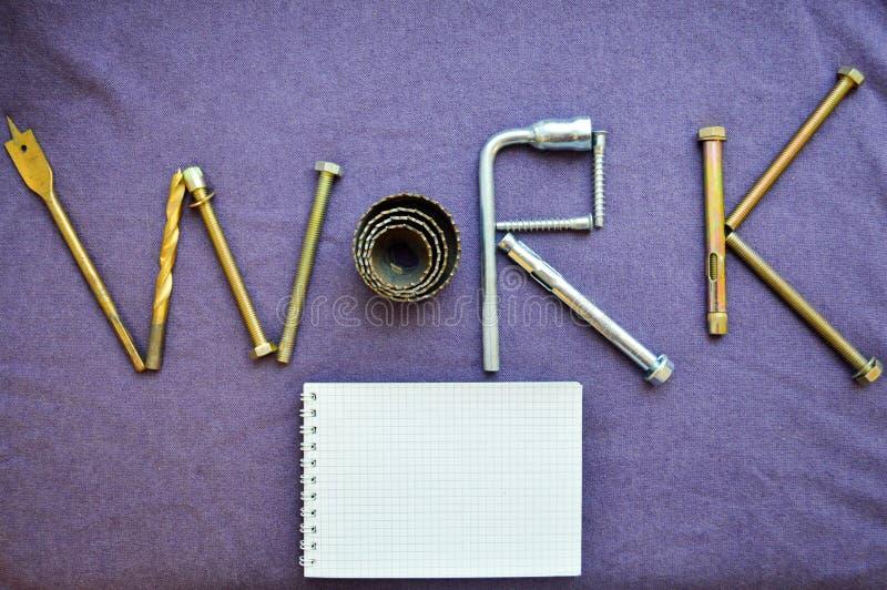 题字`工作`由金属制品工具和笔记薄写 免版税库存图片