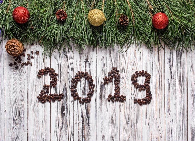 题字2019由松果做成在一个白色木背景和雪松锥体,与圣诞节玩具的杉木分支,新年 库存图片