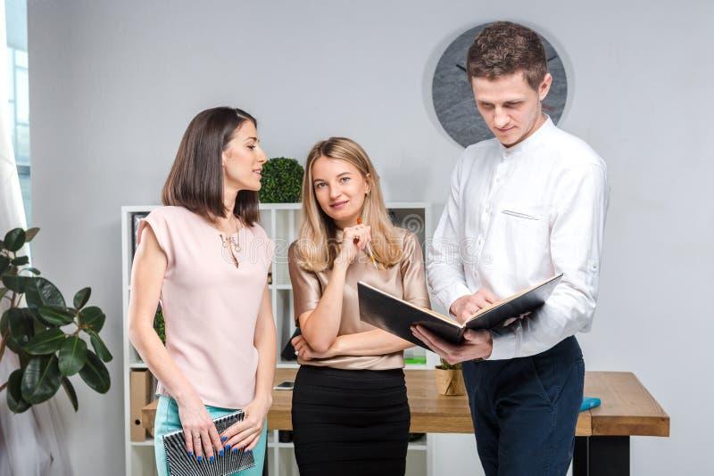 题材事务、配合和合作 一个小组年轻人,三人,立场在桌附近的一个办公室 免版税库存图片