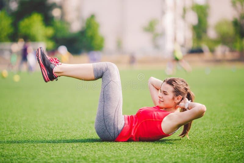 题材体育和健康 做准备的年轻美丽的白种人妇女,给肌肉加热,腹肌锻炼,丢失的腹部 免版税库存照片